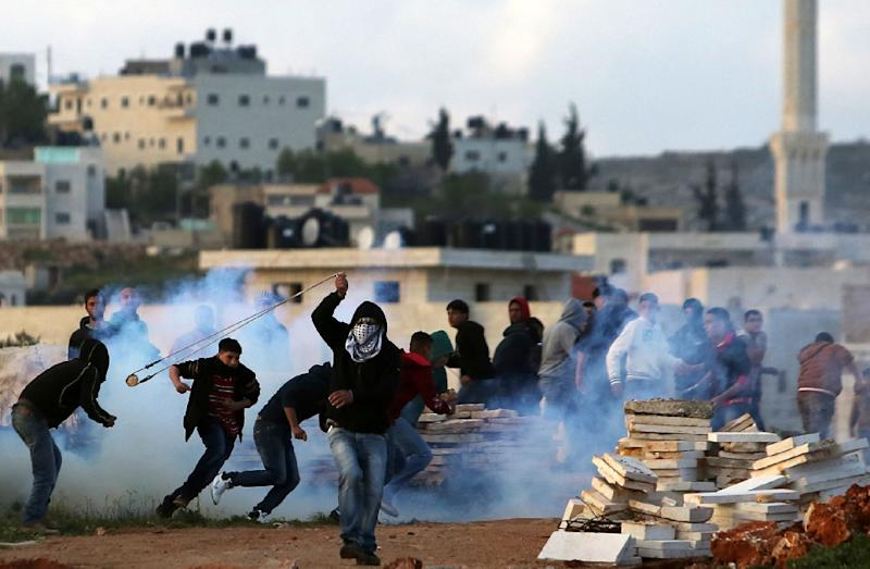 A Palestinian demonstrator throws a rock towards Israeli security forces (unseen) during clashes following a protest against the expansion of settlements on March 20, 2015, in the West Bank village of Silwad, north of Ramallah