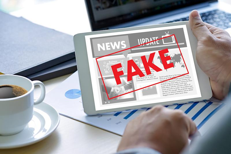 Cropped Hand Holding Fake News In Digital Tablet