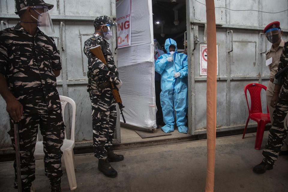 A counting agent in protective suit stands as security men guard during the counting of votes of Assam state assembly election in Gauhati, India, Sunday, May 2, 2021. With Indian hospitals struggling to secure a steady supply of oxygen, and more COVID-19 patients dying amid the shortages, a court in New Delhi said it would start punishing government officials for failing to deliver the life-saving items. (AP Photo/Anupam Nath)