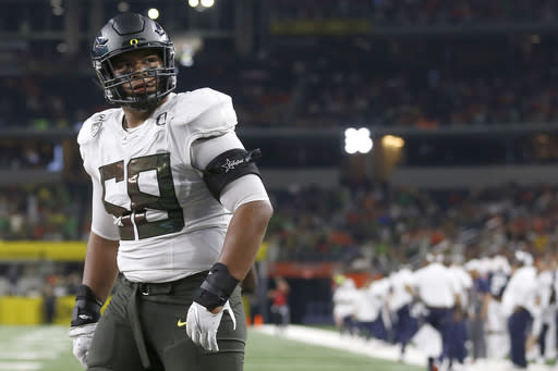 FILE - In this Aug. 31, 2019, file photo, Oregon offensive lineman Penei Sewell (58) looks on as Oregon plays Auburn in an NCAA college football game in Arlington, Texas. After the Power Five conference commissioners met Sunday, Aug. 9, 2020, to discuss mounting concern about whether a college football season can be played in a pandemic, players took to social media to urge leaders to let them play. to discuss mounting concern about whether a college football season can be played in a pandemic, players took to social media to urge leaders to let them play. (AP Photo/Ron Jenkins, File)