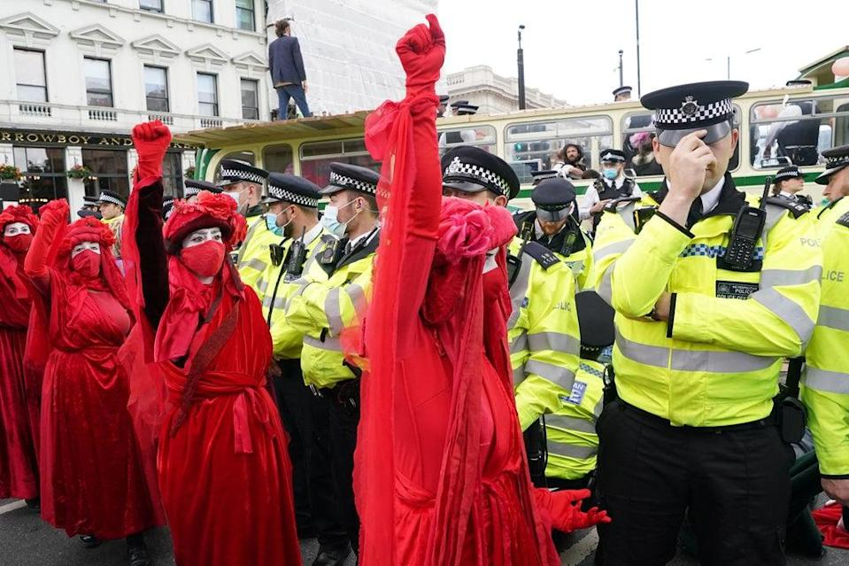 Police and demonstrators with a bus parked on London Bridge in central London during a protest by members of Extinction Rebellion (Ian West/PA) (PA Wire)