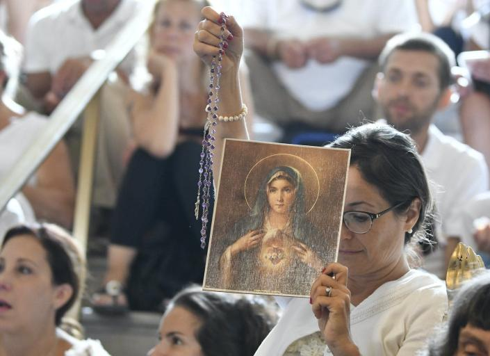 """<span class=""""caption"""">A woman holds a rosary and a picture of the Virgin Mary during a 2019 hearing in Albany, N.Y., challenging the constitutionality of the state's repeal of the religious exemption to vaccination.</span> <span class=""""attribution""""><a class=""""link rapid-noclick-resp"""" href=""""https://newsroom.ap.org/detail/VaccineExemptions/53d614f44967478da043ea27ef4e392d/photo?Query=religious%20vaccine%20exemption&mediaType=photo&sortBy=&dateRange=Anytime&totalCount=107&currentItemNo=8"""" rel=""""nofollow noopener"""" target=""""_blank"""" data-ylk=""""slk:AP Photo/Hans Pennink"""">AP Photo/Hans Pennink</a></span>"""
