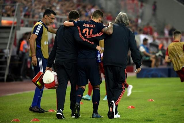 Bayern Munich's French defender Lucas Hernandez (C) limps off the pitch after injury at Olympiakos on Tuesday. (AFP Photo/ARIS MESSINIS)