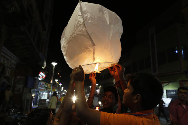 Residents light lamps to celebrate the verdict in a decades-old land title dispute between Muslims and Hindus, in Ayodhya, India , Saturday, Nov. 9, 2019. India's Supreme Court on Saturday ruled in favor of a Hindu temple on a disputed religious ground and ordered that alternative land be given to Muslims to build a mosque. The dispute over land ownership has been one of the country's most contentious issues. (AP Photo/Rajesh Kumar Singh)