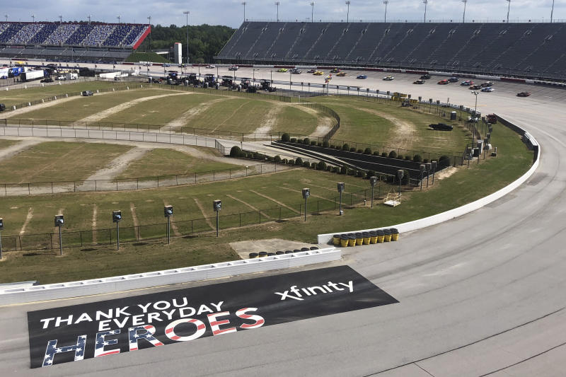 Cars go through a turn past a sign thanking people working during the coronavirus pandemic at Darlington Raceway Sunday, May 17, 2020, in Darlington, S.C. NASCAR, which has been idle for 10 weeks because of the pandemic, made its return with the Real Heroes 400 Nascar Cup Series auto race. (AP Photo/Jenna Fryer)