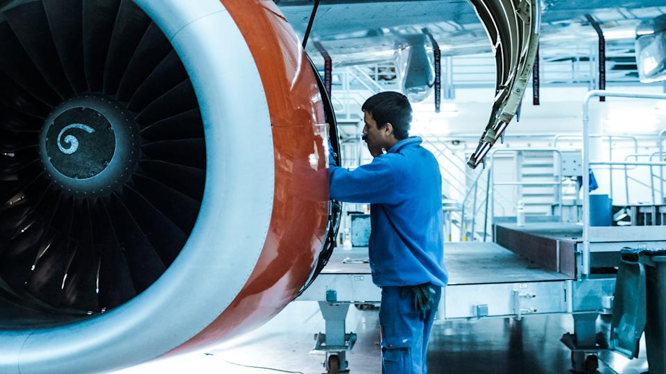 Aircraft maintenance mechanic inspects and tunes plane engine in a hangar.