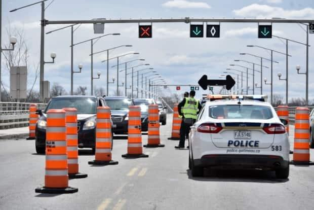Police oversee a checkpoint on the Quebec side of the Champlain Bridge between Ottawa and Gatineau, Que., in May 2020. The Ontario government has announced the checkpoints will return Monday at its interprovincial border crossings with Quebec and Manitoba. (Jonathan Dupaul/CBC - image credit)