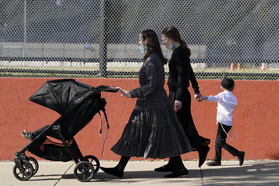 FILE - In this Oct. 4, 2020, file photo, two women walk with children during the Jewish holiday of Sukkot in the Borough Park neighborhood of the Brooklyn borough of New York. Amid a new surge of COVID-19 in New York's Orthodox Jewish communities, many residents are reviving health measures that some had abandoned over the summer – social distancing, wearing masks. For many, there's also a return of anger: They feel the city is singling them out for criticism that other groups avoid. (AP Photo/Kathy Willens, File)