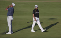 South Africa's Louis Oosthuizen, right watches as Spain's Jon Rahm reacts to his putt on the 18th green during the second round of the British Open Golf Championship at Royal St George's golf course Sandwich, England, Friday, July 16, 2021. (AP Photo/Ian Walton)