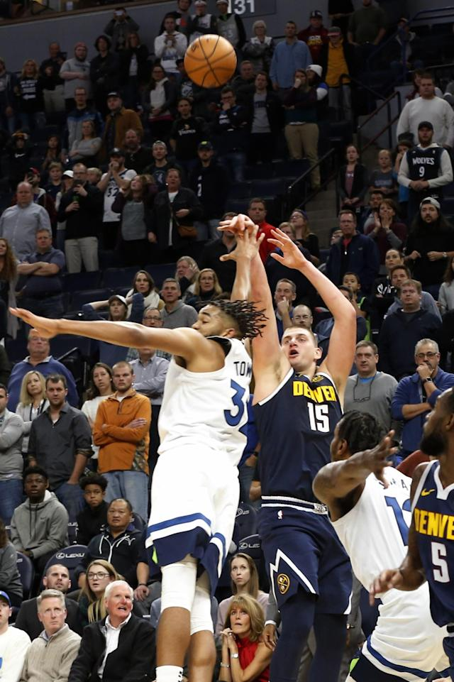 Denver Nuggets' Nikola Jokic, right, of Serbia, shoots the go-ahead basket over Minnesota Timberwolves' Karl-Anthony Towns in the final seconds in overtime of an NBA basketball game Sunday, Nov. 10, 2019, in Minneapolis. The Nuggets won 100-98. (AP Photo/Jim Mone)
