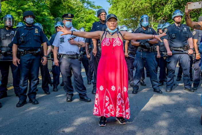 A person stands, arms raised to the side, in front of a row of police.