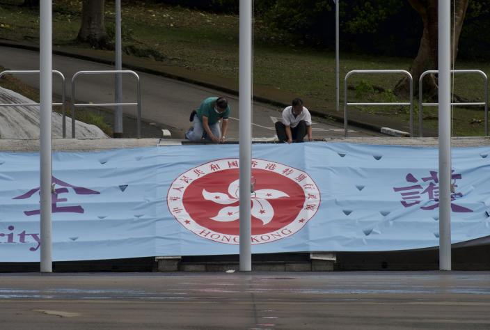 """Workers fix a banner with a Hong Kong logo on the National Security Education Day at a police school in Hong Kong Thursday, April 15, 2021. Beijing's top official in Hong Kong on Thursday warned foreign forces not to interfere with the """"bottom line"""" of national security in Hong Kong, threatening retaliation even amid ongoing tensions between China and Western powers. (AP Photo/Vincent Yu)"""
