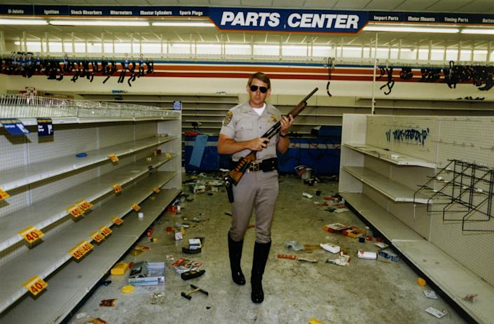 """Officer Hugh Gnecco of the California Highway Patrol checks for looters in an auto parts store at Washington Boulevard and Western Avenue during the L.A. riots on May 1, 1992.<span class=""""copyright"""">Rick Meyer—Los Angeles Times/Getty Images</span>"""