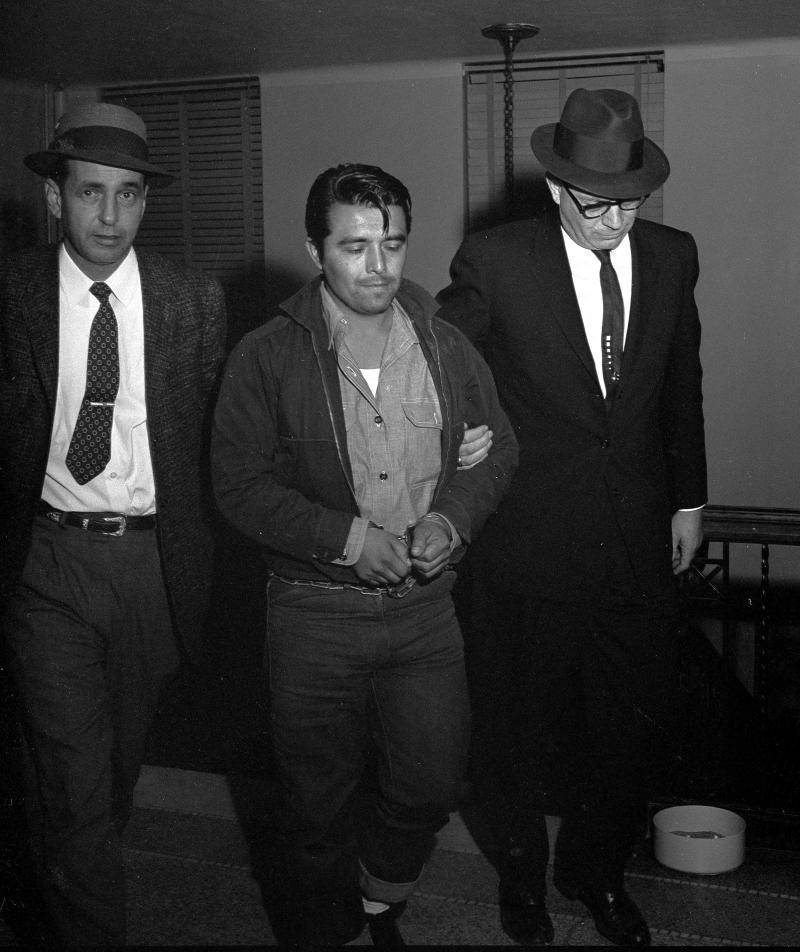 "FILE - In this Jan. 6, 1960 file photo, Perry Edward Smith is led by police officers into the courthouse at Garden City, Kan. Smith was arrested in Las Vegas and charged with first degree murder in the slaying of four members of the Herbert Clutter family at their farm house in Holcomb, Kan. Fifty years ago, the Clutter murders inspired Truman Capote to write ""In Cold Blood"".  A Florida detective wants to exhume the bodies of Edward Smith and accomplice Richard Hickock to see if there is evidence linking the two men to the 1959 murders of four in a rural community south of Sarasota. (AP Photo/William Straeter, FILE)"