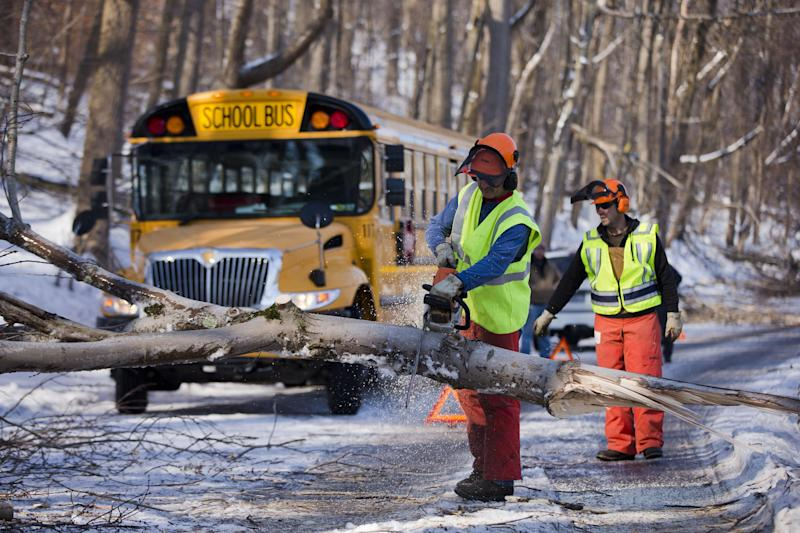 FILE - In this Friday, Feb. 7, 2014 file photo workmen clear a downed tree blocking a school bus in the aftermath of a winter storm, in Downingtown, Pa. Schools canceling classes because of winter weather in at least 10 states have used up the wiggle room in their academic calendars, forcing them to schedule makeup days or otherwise compensate for the lost time. (AP Photo/Matt Rourke, File)