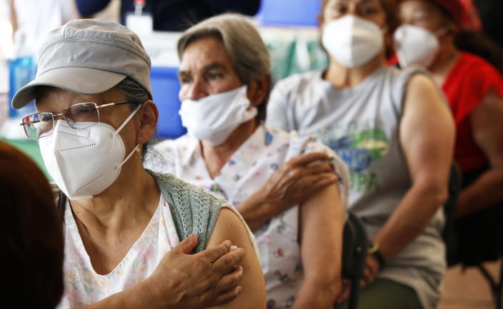 Persons over 60-years-old wait in observation after receiving their second dose of the AstraZeneca COVID-19 vaccine at the University Olympic Stadium in Mexico City, Monday, April 12, 2021. (AP Photo/Marco Ugarte)