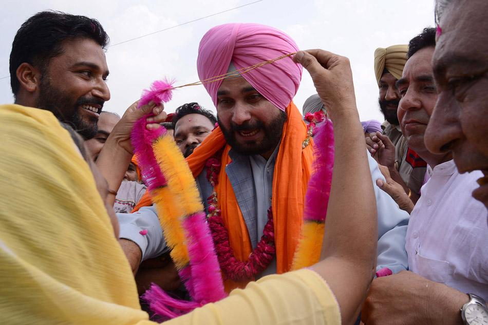 Members of the Bharatiya Janata Party (BJP) garland former Indian cricketer and member of parliament Navjot Singh Sidhu (C) on his return after remaining absent from his constituency for more than eight months, in Amritsar on September 4, 2013.   AFP PHOTO/NARINDER NANU        (Photo credit should read NARINDER NANU/AFP/Getty Images)