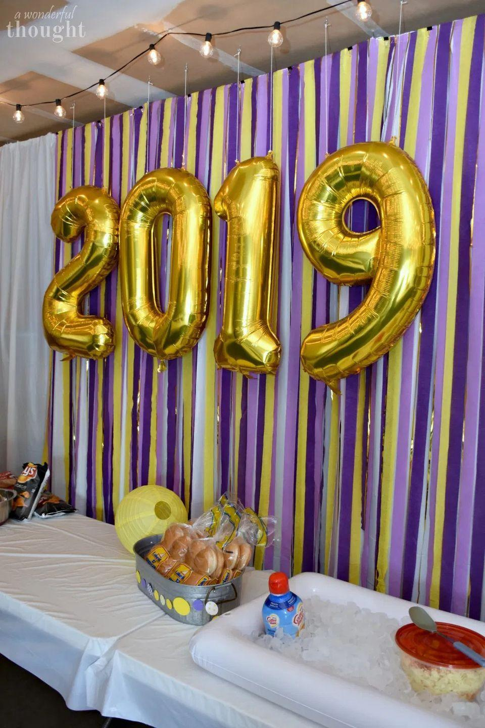 "<p>All that great food at the graduation party should really be spotlighted with an eye-catching backdrop! All you need are colorful streamers and balloons with their graduating year. </p><p><strong>Get the tutorial at <a href=""https://awonderfulthought.com/graduation-party-ideas-garage-party/"" rel=""nofollow noopener"" target=""_blank"" data-ylk=""slk:A Wonderful Thought"" class=""link rapid-noclick-resp"">A Wonderful Thought</a>.</strong></p><p><a class=""link rapid-noclick-resp"" href=""https://go.redirectingat.com?id=74968X1596630&url=https%3A%2F%2Fwww.walmart.com%2Fip%2FPurple-81-ft-Solid-Crepe-Streamer%2F298224428&sref=https%3A%2F%2Fwww.thepioneerwoman.com%2Fhome-lifestyle%2Fentertaining%2Fg36014713%2Fgraduation-party-ideas%2F"" rel=""nofollow noopener"" target=""_blank"" data-ylk=""slk:SHOP STREAMERS"">SHOP STREAMERS</a></p>"