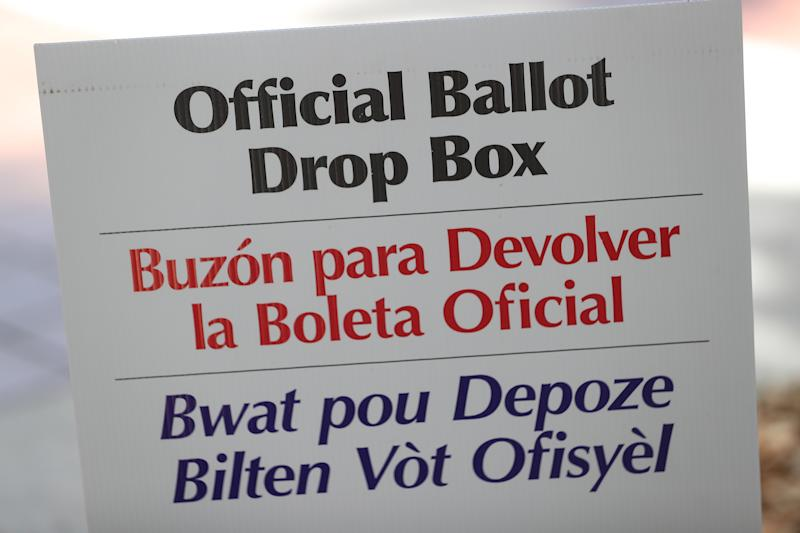 A sign directs voters to an official Miami-Dade County ballot drop box where they can cast their vote by placing their mail-in ballots inside the box on August 11, 2020 in Miami, Florida. (Joe Raedle/Getty Images)