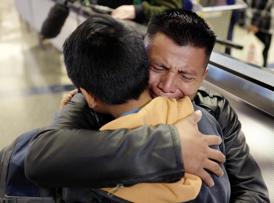 FILE - In this Jan. 22, 2020 file photo, David Xol-Cholom of Guatemala hugs his son, Byron, at Los Angeles International Airport as they reunite after being separated about one-and-half years ago during the Trump administration's wide-scale separation of immigrant families. On Friday, Feb. 5, 2021, The Associated Press reported on stories circulating online incorrectly asserting that nine parents who were deported under the Trump administration after being separated from their children at the border were allowed to return to the United States on Wednesday, Feb. 3, 2021. The family reunions referenced on social media did not happen this week, they occurred in 2020 due to a court order. (AP Photo/Ringo H.W. Chiu)
