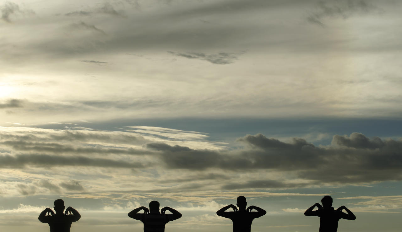 A group of men perform physical exercise training as sun set at Galle Face green in Colombo January 9, 2013. REUTERS/Dinuka Liyanawatte (SRI LANKA - Tags: SOCIETY TPX IMAGES OF THE DAY)