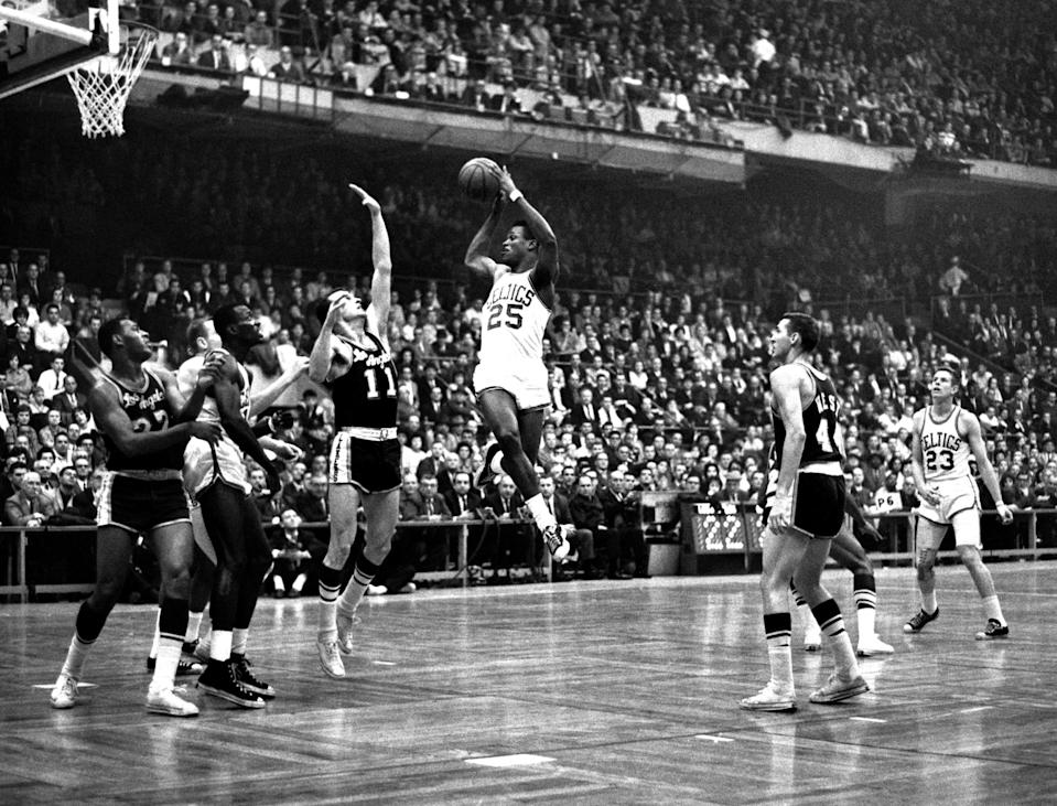 K.C. Jones looks to shoot as Frank Selvy of the Los Angeles Lakers goes for the block in a 1960s game.