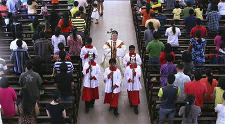 A priest and altar boys walk down the aisle after prayers were conducted during a mass service inside the church of Our Lady of Lourdes at Klang, outside Kuala Lumpur