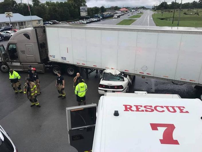 Police in Tennessee said a driver had to be cut from a car after getting wedged under a semi-truck on Wednesday.