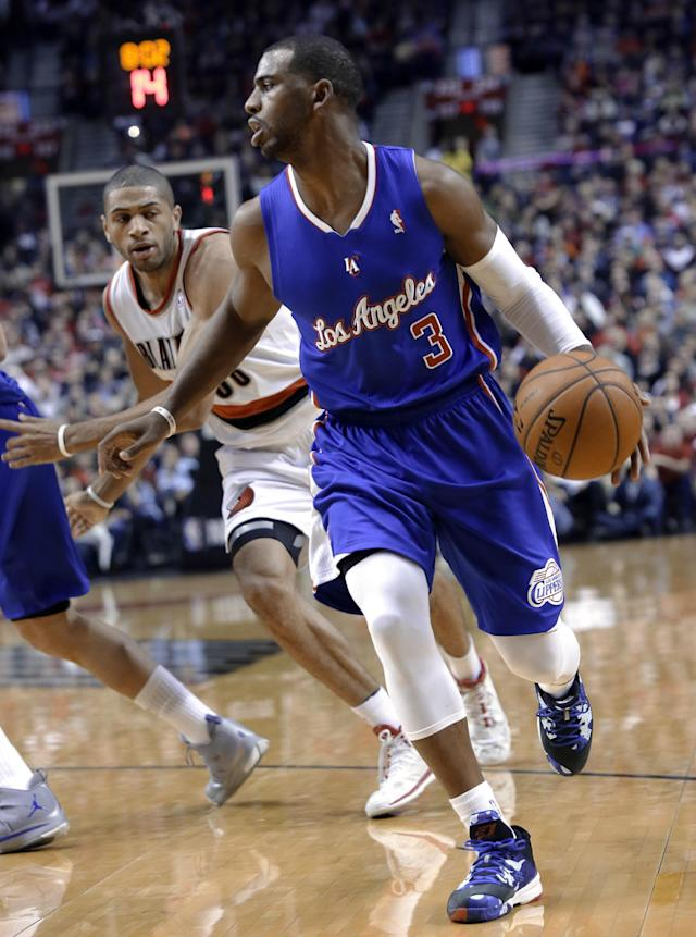 Los Angeles Clippers guard Chris Paul, right, drives past Portland Trail Blazers forward Nicolas Batum during the first half of an NBA basketball game in Portland, Ore., Thursday, Dec. 26, 2013. (AP Photo/Don Ryan)