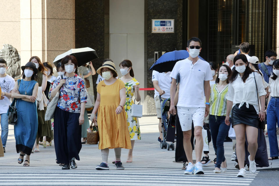 People wearing face masks to protect against the spread of the coronavirus walk on a street in Tokyo Saturday, July 24, 2021. (AP Photo/Koji Sasahara)