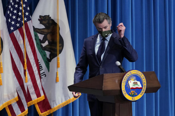 """FILE - In this Jan. 8, 2021, file photo, California Gov. Gavin Newsom removes his face mask during a news conference in Sacramento, Calif. Gov. Newsom said Tuesday, May 11, 2021, the nation's most populous state would stop requiring people to wear masks in almost all circumstances on June 15, describing a world he said will look """"a lot like the world we entered into before the pandemic."""" (AP Photo/Rich Pedroncelli, Pool, File)"""