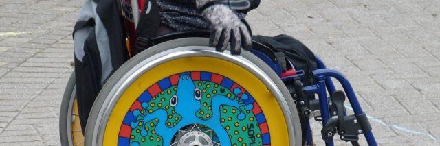 Manual wheelchair user with colorfully-decorated wheels.