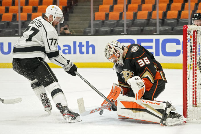 Anaheim Ducks goaltender John Gibson, right, stops a shot by Los Angeles Kings center Jeff Carter during the first period of an NHL hockey game Monday, March 8, 2021, in Anaheim, Calif. (AP Photo/Mark J. Terrill)