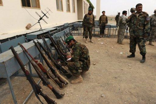 An Afghan National Army (ANA) soldier inspects seized guns recovered during a house-to-house search in Khost