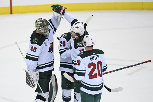 Minnesota Wild goaltender Devan Dubnyk (40) celebrates with defenseman Greg Pateryn (29), left wing Marcus Foligno (17), and defenseman Ryan Suter (20) after the team's NHL hockey game against the Washington Capitals, Friday, March 22, 2019, in Washington. The Wild won 2-1. (AP Photo/Nick Wass)