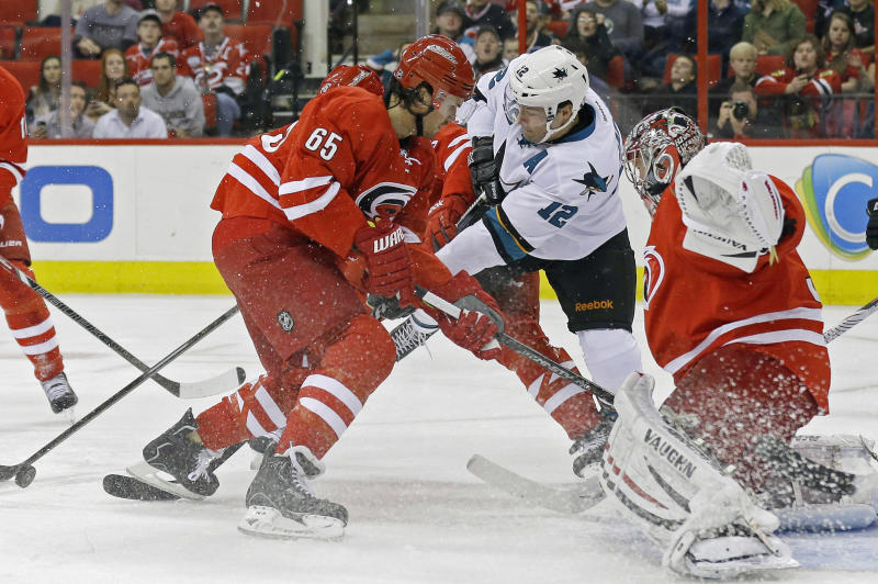 Carolina Hurricanes' Ron Hainsey (65) and goalie Cam Ward defend against San Jose Sharks' Patrick Marleau (12) during the first period of an NHL hockey game in Raleigh, N.C., Friday, Dec. 6, 2013. (AP Photo/Gerry Broome)