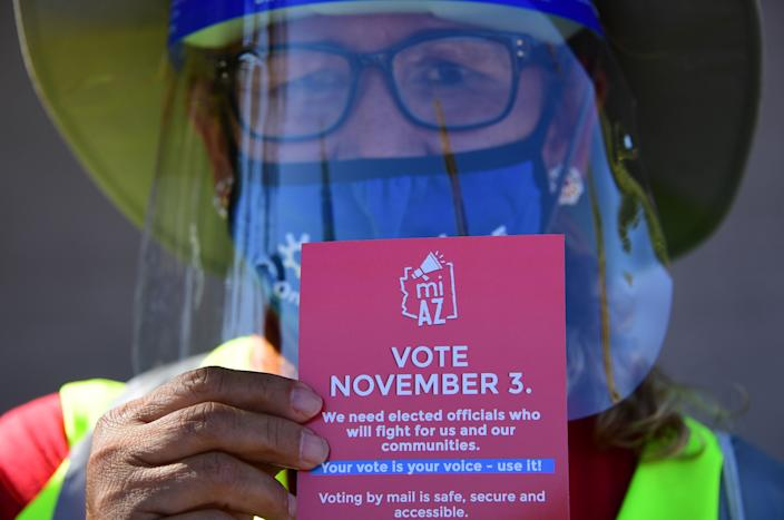 A Democratic Party canvasser holds up campaign material while knocking on doors in the suburbs of Phoenix on Oct. 15, 2020, to encourage people to vote in the presidential and congressional elections.
