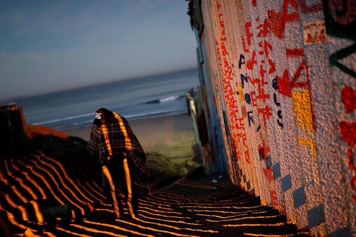 A migrant walks along the border fence between Mexico and the United States in Tijuana on Nov. 15. (Photo: Carlos Garcia Rawlins/Reuters)