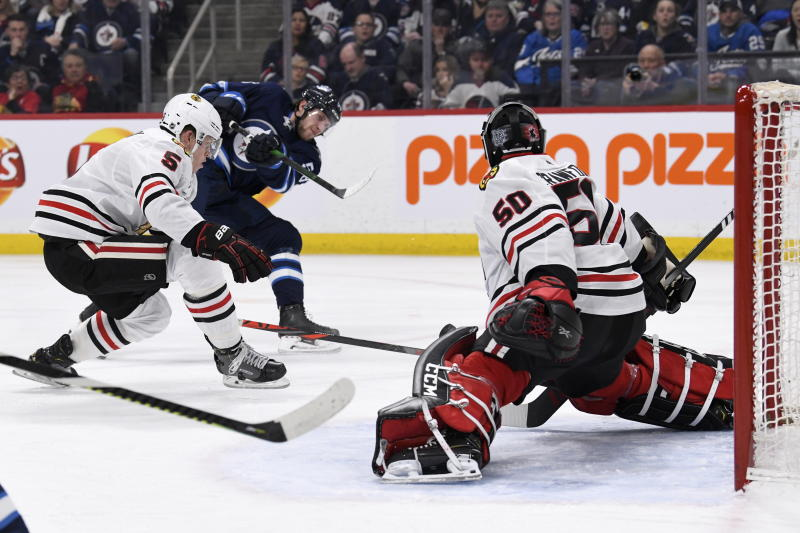 Chicago Blackhawks goaltender Corey Crawford (50) makes a save on Winnipeg Jets' Jansen Harkins, rear, during the second period of an NHL hockey game Sunday, Feb. 16, 2020, in Winnipeg, Manitoba. (Fred Greenslade/The Canadian Press via AP)