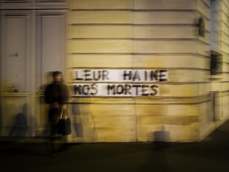 "Sarah stands next to slogan reading ""Their hate, our dead"" in Paris. Under cover of night, activists have glued slogans to the walls of buildings to draw attention to domestic violence, a problem French President Emmanuel Macron has called ""France's shame."" (Photo: Kamil Zihnioglu/AP)"