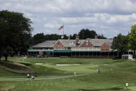 A group walks down the fairway in front of the clubhouse at the Inverness Golf Club during the first round of the LPGA Drive On Championship golf tournament in Toledo, Ohio, Friday, July 31, 2020. The tournament is being played with no fans due to COVID-19 safety protocol. (AP Photo/Gene J. Puskar)
