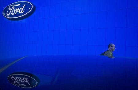 A man walks past new Ford car at Jacob Javits Convention Center during New York International Auto Show in New York