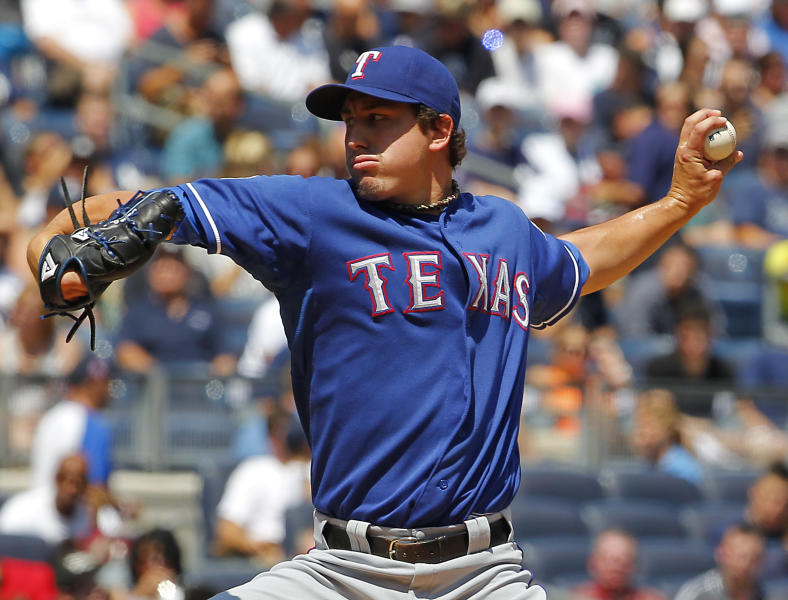 Texas Rangers starter Derek Holland throws a pitch in the third inning of a Baseball game against the New York Yankees at Yankee Stadium in New York, Thursday, Aug. 16, 2012. (AP Photo/Paul J. Bereswill)