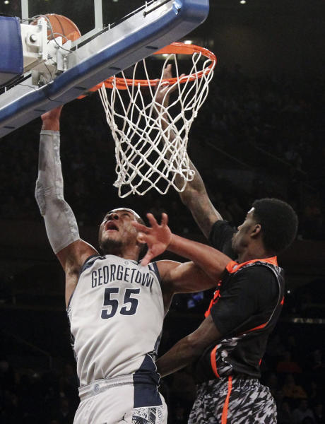Georgetown's Jabril Trawick, left, shoots as Cincinnati's Shaquille Thomas defends during the first half of an NCAA college basketball game at the Big East Conference tournament, Thursday, March 14, 2013 in New York. (AP Photo/Mary Altaffer)