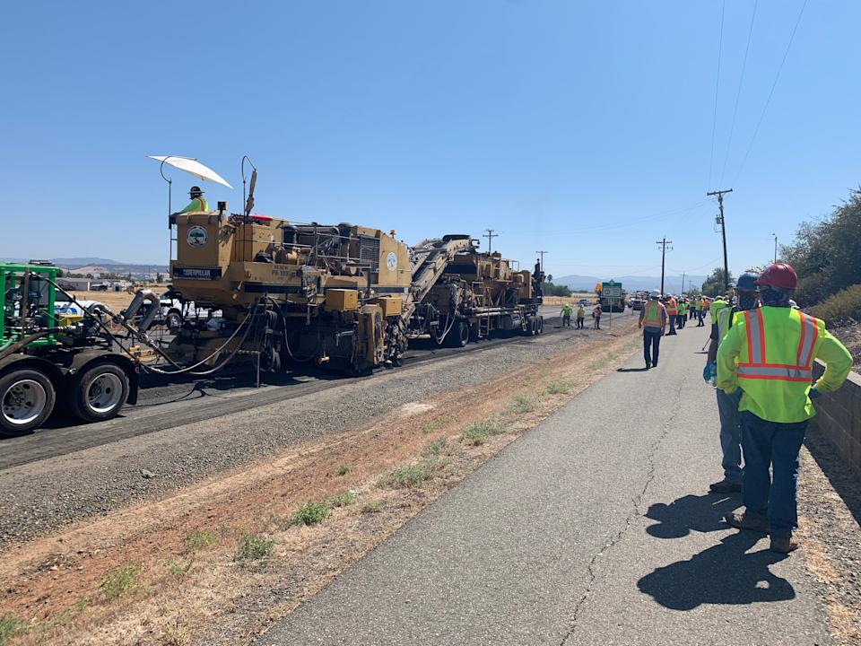 """The """"recycling train'' scoops up the old asphalt, grinds it, blends it with a binder and lays it down to form the new pavement."""