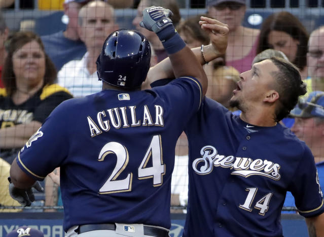 Milwaukee Brewers' Jesus Aguilar (24) celebrates with Hernan Perez as he returns to the dugout after hitting a solo home run off Pittsburgh Pirates starting pitcher Jameson Taillon during the fourth inning of a baseball game in Pittsburgh, Thursday, July 12, 2018. (AP Photo/Gene J. Puskar)