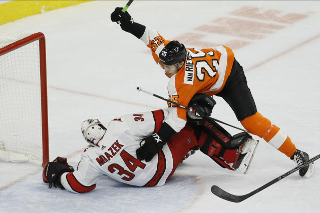 Philadelphia Flyers' James van Riemsdyk (25) collides with Carolina Hurricanes' Petr Mrazek (34) during the first period of an NHL hockey game, Tuesday, Nov. 5, 2019, in Philadelphia. (AP Photo/Matt Slocum)