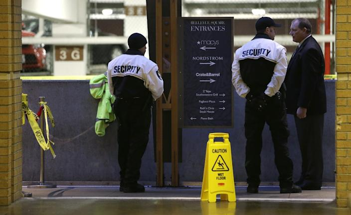 Private security officers and a mall official stand adjacent to the Munchbar Monday, Dec. 24, 2012, in Bellevue, Wash. A 30-year-old Seattle man was killed and another man wounded in a shooting at the crowded bar earlier in the morning, police said. AP Photo/Elaine Thompson)
