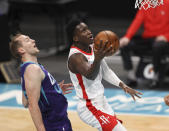 Houston Rockets guard Victor Oladipo, right, drives to the basket past Charlotte Hornets center Cody Zeller in the first half of an NBA basketball game in Charlotte, N.C., Monday, Feb. 8, 2021. (AP Photo/Nell Redmond)