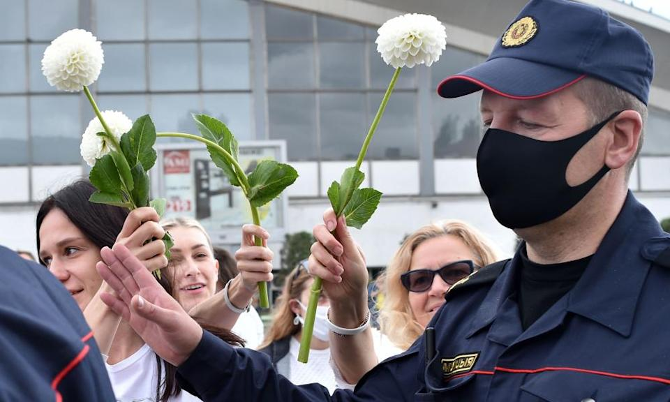 Women protesters offer flowers to police officers during a demonstration.